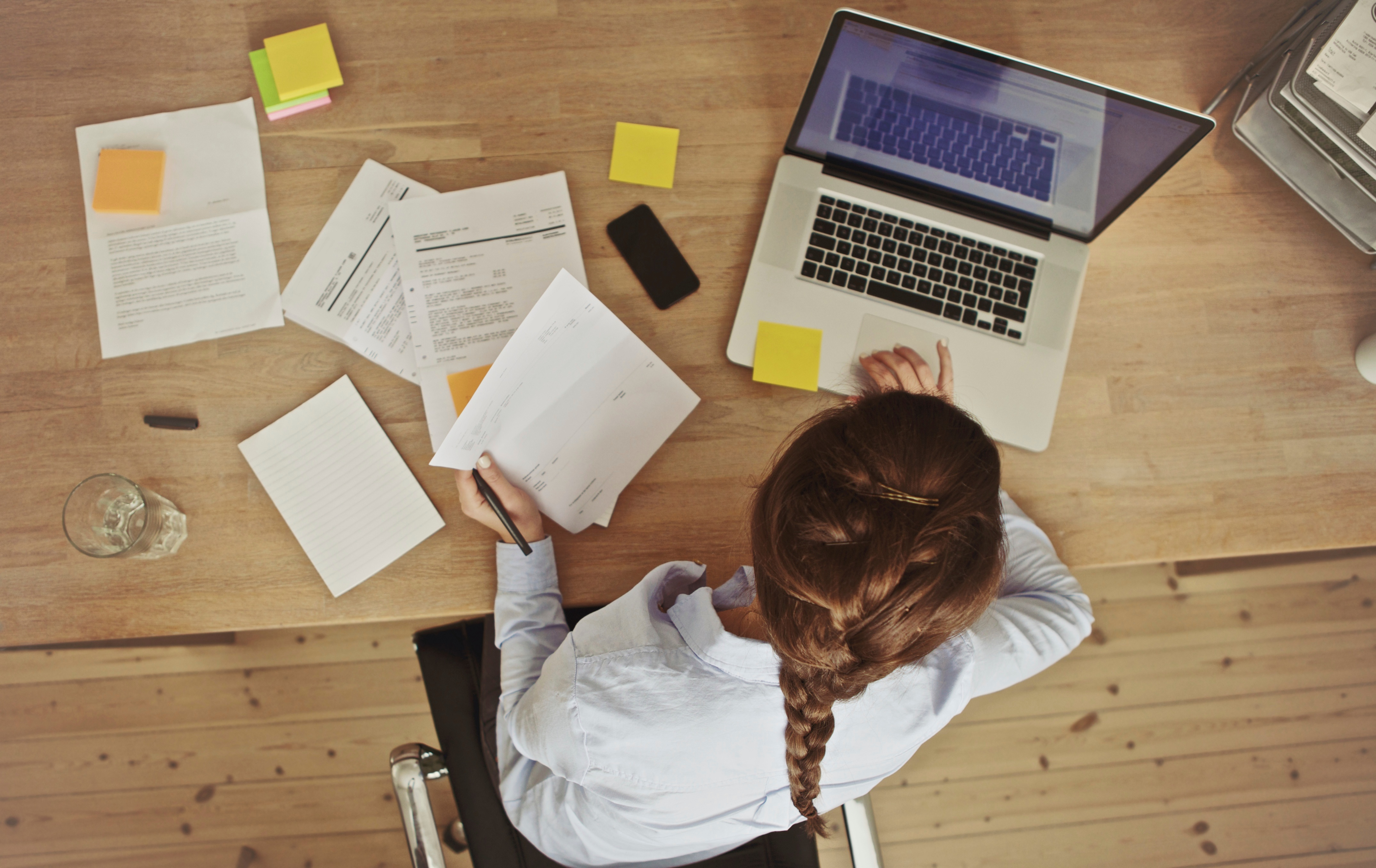 Businesswoman-working-at-her-office-desk-with-documents-and-laptop-000031045570_Large.jpg
